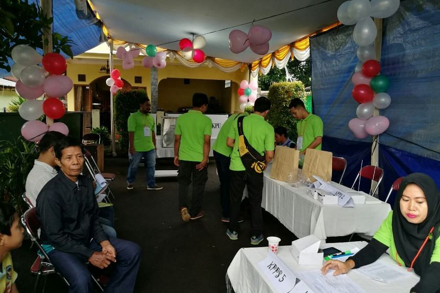 Voters and officials at the polling station in Cipayung, East Jakarta.