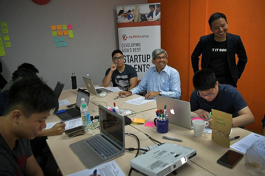 Dr Yaacob (second from left) at an Alpha Camp class with students (from left) Ashleigh Rhazaly and Ng Yao Min and the school's chief executive Bernard Chan (standing). The school equips students with skills to enter the information and communications