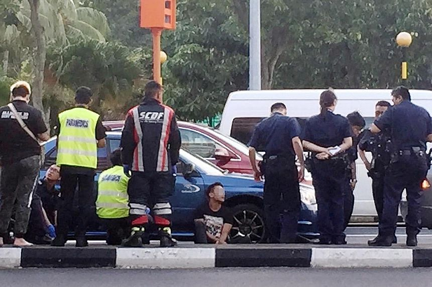 The arrested man, who allegedly wielded an electroshock weapon, is seen sitting on the road flanked by police and SCDF officers. Police investigations are ongoing in the case, the latest in a spate of incidents involving drivers of rental cars.