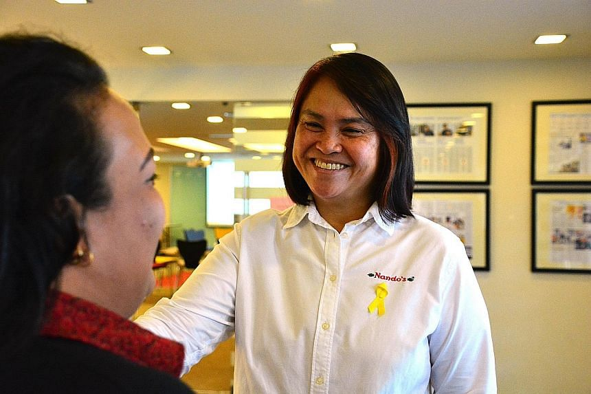 Nando's CEO June Koh talking to one of her staff, Ms Moon, who is a former offender. Ms Koh's support for them is now being shared by a growing pool of employers, according to latest prison annual figures.