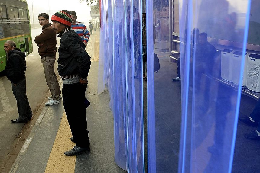 Commuters at a bus stop in New Delhi where air purifiers have been installed.