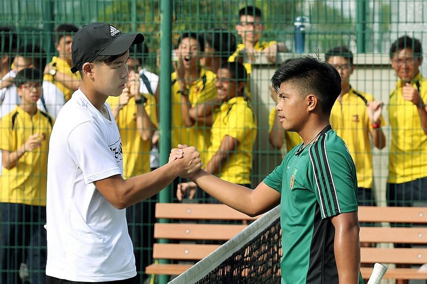 ACS(I) captain Robin Cheng (left) shaking hands with Raffles Institution's Naqib Ahmad after defeating his rival 6-4, 6-3 in the Schools National B Division Tennis Championship at Kallang yesterday. His victory tied the scores at 2-2, setting up team