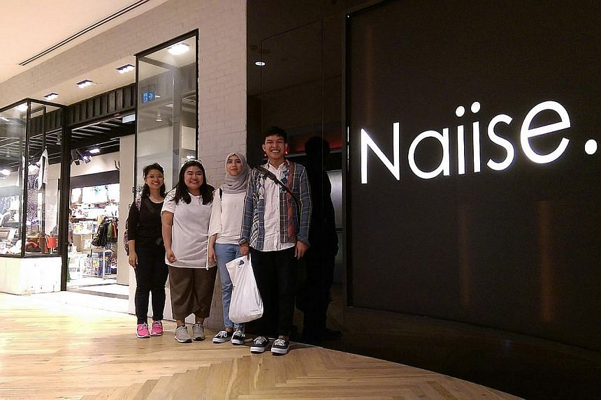 (From far left) Ms Ida Ayu Farina, 24; Ms Ari Suci, 23; Ms Lintang and Mr Radike outside the Naiise outlet in Orchard Gateway. The Indonesian visitors are here for goods made or designed in Singapore.