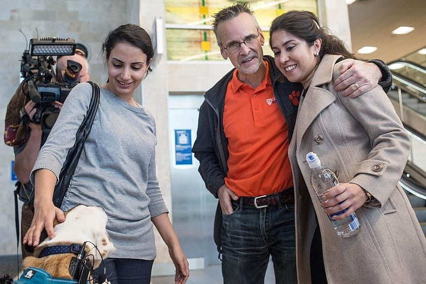 Iranian engineer Nazanin Zinouri (at right) being greeted by her former Clemson University adviser Kevin Taaffe after arriving at an airport in South Carolina earlier this month. While trying to return to South Carolina after visiting her family in I