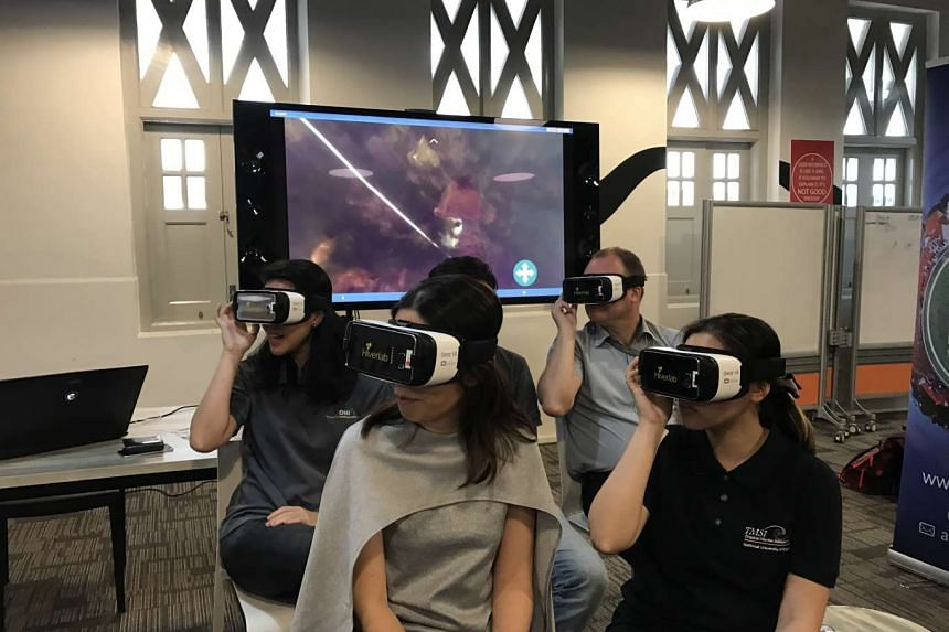 Participants testing out a new virtual reality programme which trains people in reef monitoring before an actual dive.