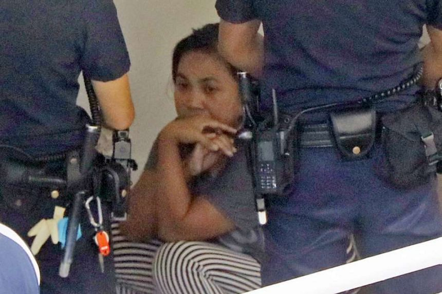 The maid, seen here with police on Monday, will be charged in court on Feb 15 with murder.