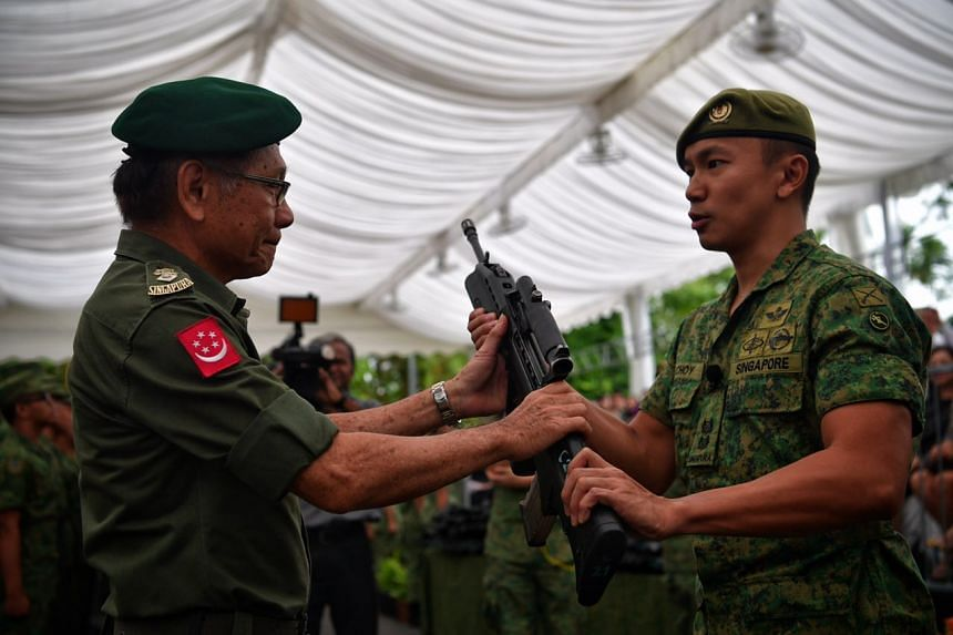 71-year-old SAF veteran LTC (retired) Swee Boon Chai hands CO LTC Choy Yong Cong a rifle during the weapon presentation ceremony held before the launch of Syonan Gallery: War and its Legacies at the Former Ford Factory in Upper Bukit Timah.