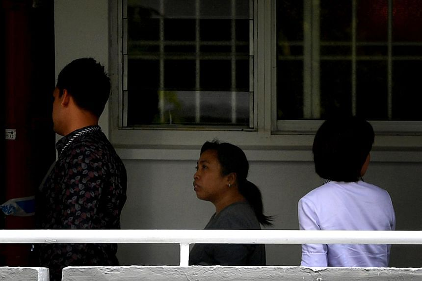 An Indonesian maid (centre) was charged in court with murder after an elderly woman was found dead in a Tampines flat on Monday.