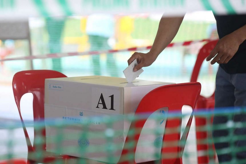 A man drops his vote into the box at Blk 105A Bukit Batok Central during the Bukit Batok by-election on May 7, 2016.