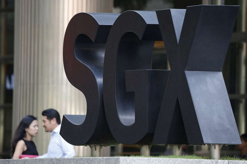 People pass an SGX Singapore Exchange logo outside its premises in Singapore's central business district