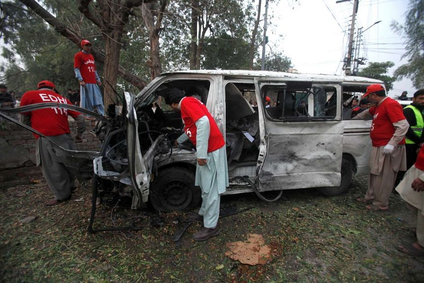 Volunteers search for remains in a vehicle at the scene of a bomb attack in Peshawar, Pakistan, Feb 15, 2017.