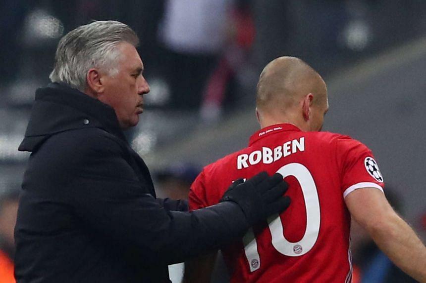 Bayern Munich's Arjen Robben walks past coach Carlo Ancelotti as he is substituted.