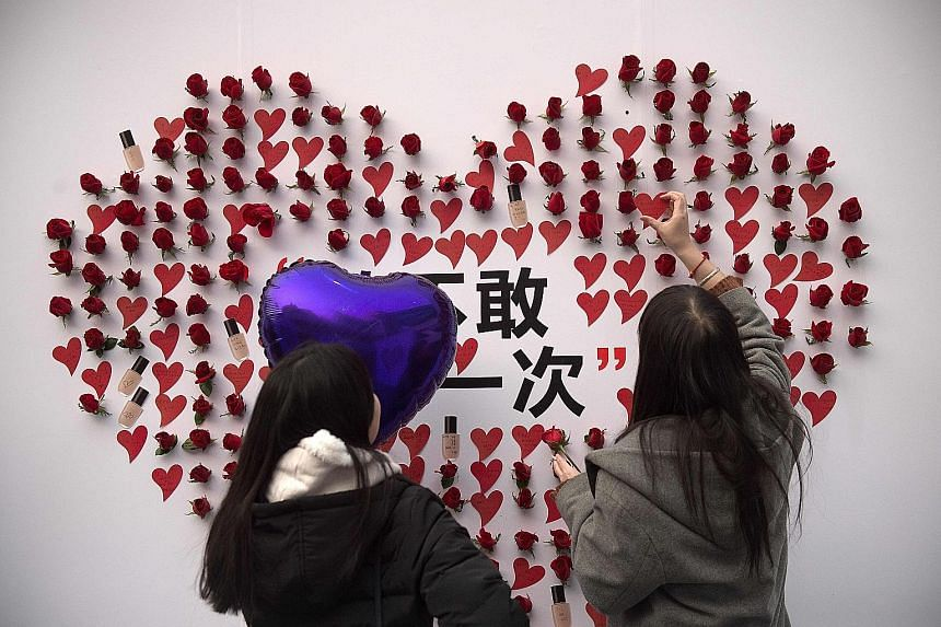 A woman placing a heart-shaped sticker at a Beijing mall on Valentine's Day, which is commercialised in big Chinese cities, but its focus on couples can leave China's singles frustrated.