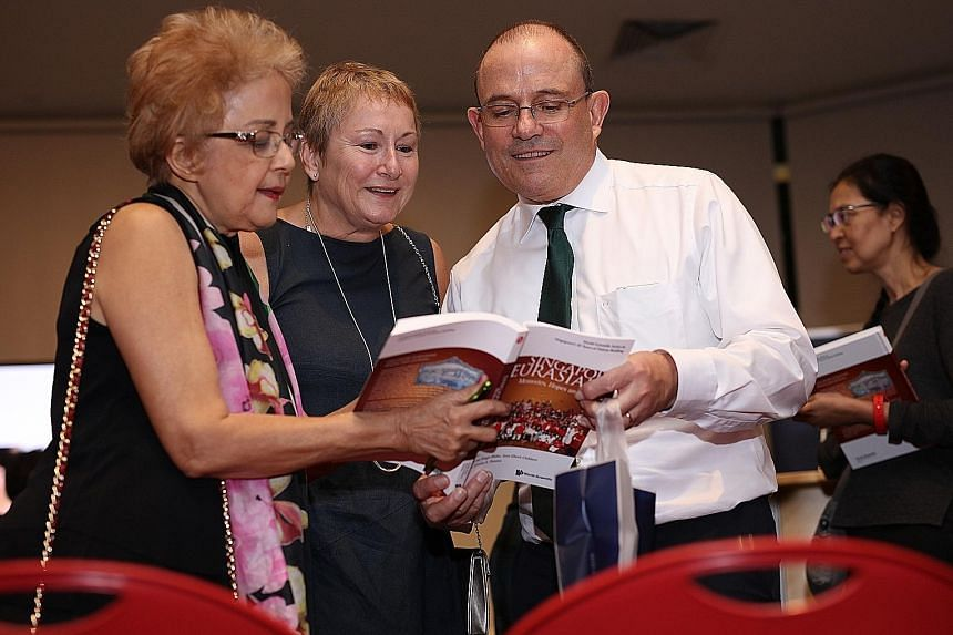 Eurasian Association member and contributing author Patricia De Souza (far left) browsing the book with Ambassador of Ireland Geoffrey Keating and his wife, Jane.
