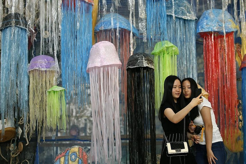 """Thai visitors taking a selfie with an art installation at the """"Heart For The Ocean: Break Free From Plastic"""" exhibition at the Bangkok Art and Culture Centre in Bangkok yesterday. The exhibition, which is on till Sunday, was made from plastic and gar"""