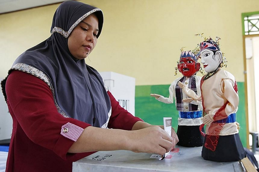 Election workers at a polling station in Jakarta. Election rules in Indonesia require candidates to win a majority of the vote, but exit polls in the Jakarta governor race point to about 80 per cent of votes evenly spread between the two leading pair