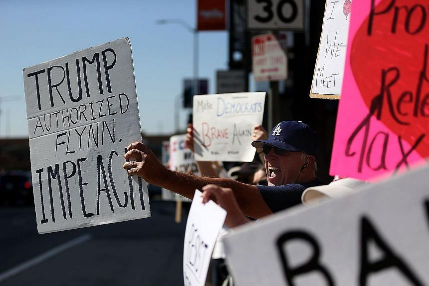 Anti-Trump demonstrators protesting in Los Angeles on Tuesday. Amid calls for an independent investigation, the White House admitted that the President was told three weeks ago that Mr Flynn may have misled colleagues about his Kremlin contacts.