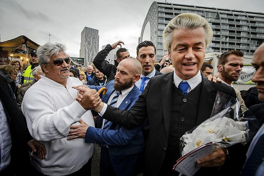 In this November 2015 file photo, Mr Geert Wilders (in suit) is seen distributing flyers to protest against accommodating refugees in Rotterdam.