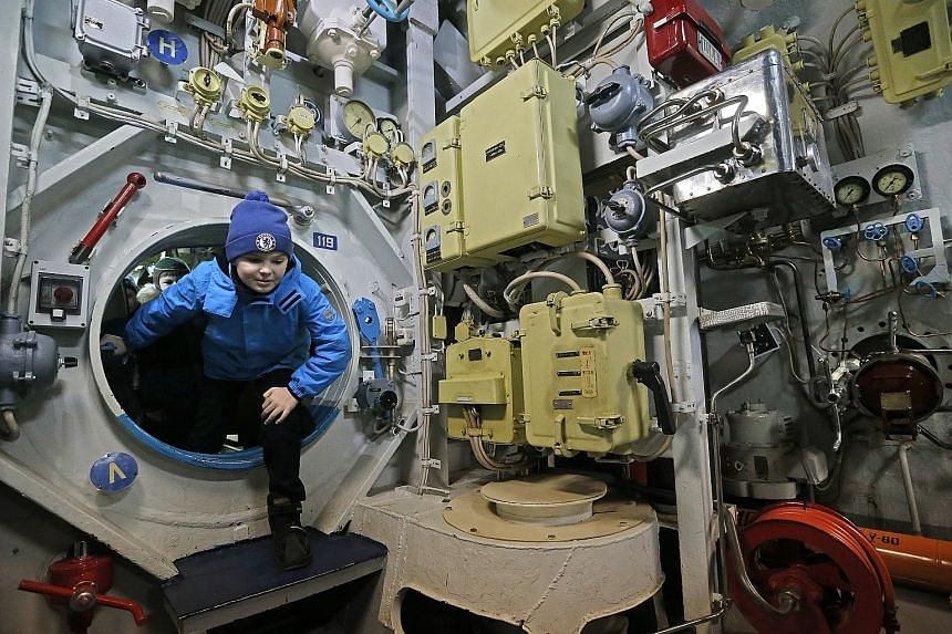 A boy climbing through the bulkhead door of a large diesel submarine as he explored the vessel during a visit by a group of children in Russia on Tuesday. The submarine- turned-museum, installed in the waters of Moscow's Khimki Reservoir, has been op
