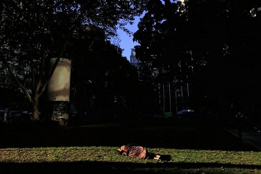 A homeless man sleeps under a blanket in a patch of sunlight at a park in central Sydney.