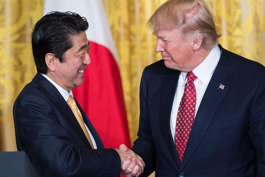 Japanese Prime Minister Shinzo Abe (left) shaking hands with US President Donald Trump in the East Room of the White House on Feb 10, 2017.