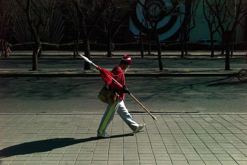 An elderly man carrying a spear walking after his morning exercise in Beijing on Feb 10, 2017.