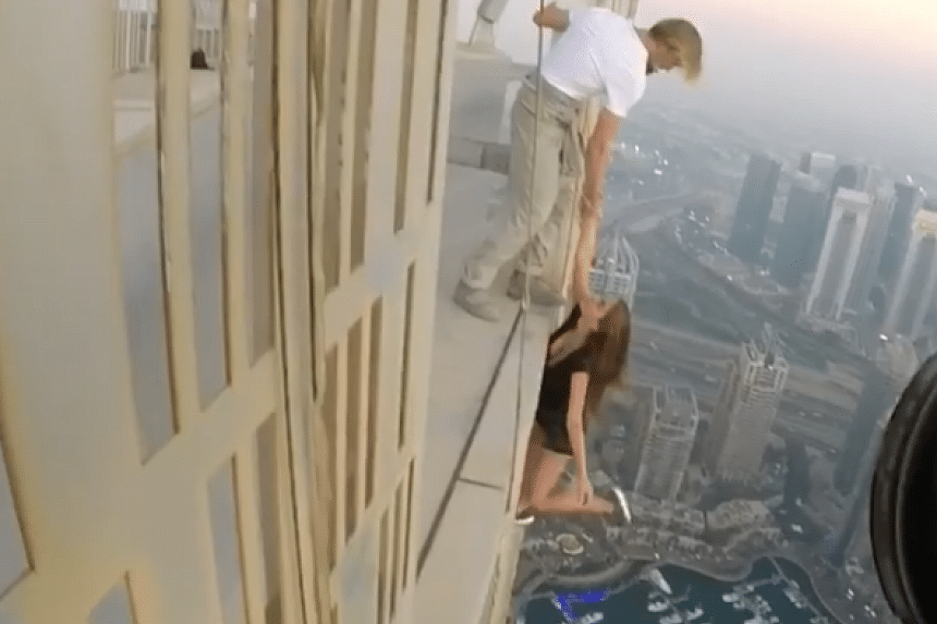 Russian model Viktoria Odintsova, 22, was filmed dangling over the side of a Dubai skyscraper, held only by a male assistant's hand and not wearing any safety equipment.