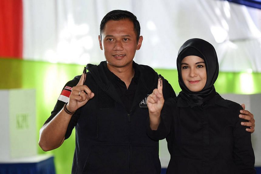 Agus Harimurti Yudhoyono (left), a candidate in the running to lead the Indonesian capital Jakarta, and his wife Annisa Pohan, show their fingers during an election for Jakarta's governor.
