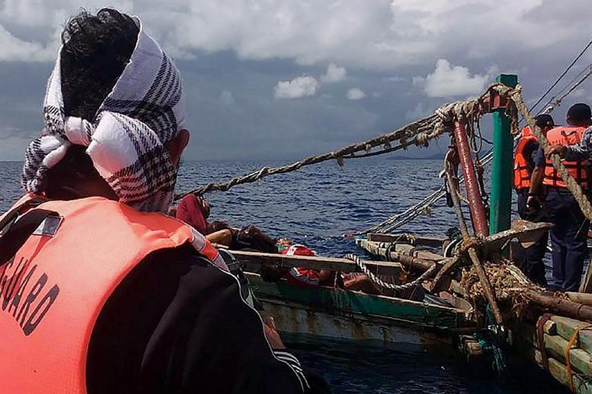 File photo of Philippine coast guards inspecting a fishing boat whose crew is suspected to have been killed by pirates off the coast of Laud Siromon in Zamboanga, the southern Philippine island of Mindanao.