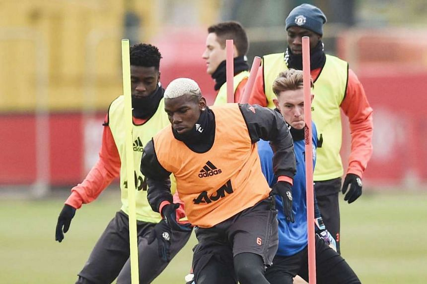 (Above) United's France midfielder Paul Pogba training with team-mates on the eve of their Europa League round of 32 first-leg game against St-Etienne, who count among their players his older brother Florentin. The siblings will meet in a professional mat