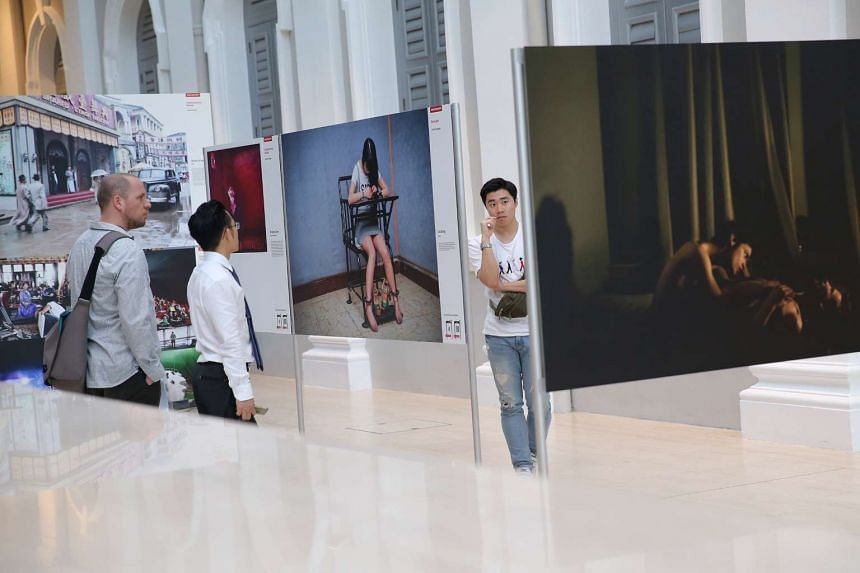 Members of the public looking at the award-winning photographs at the World Press Photo 2015 exhibition held at the National Museum of Singapore on Jan 28, 2016.