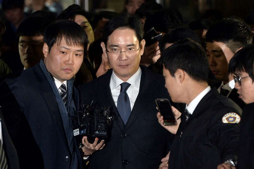 Samsung Group's heir-apparent Lee Jae Yong (centre) leaving after attending a court hearing on whether he will be issued with an arrest warrant at the Seoul Central District Court on Feb 16, 2017.