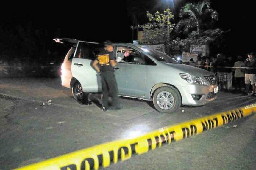 Policemen inspect the car of lawyer Mia Manuelita Mascariñas-Green, who died in an ambush staged by four men in Tagbilaran City on Wednesday (Feb 15).