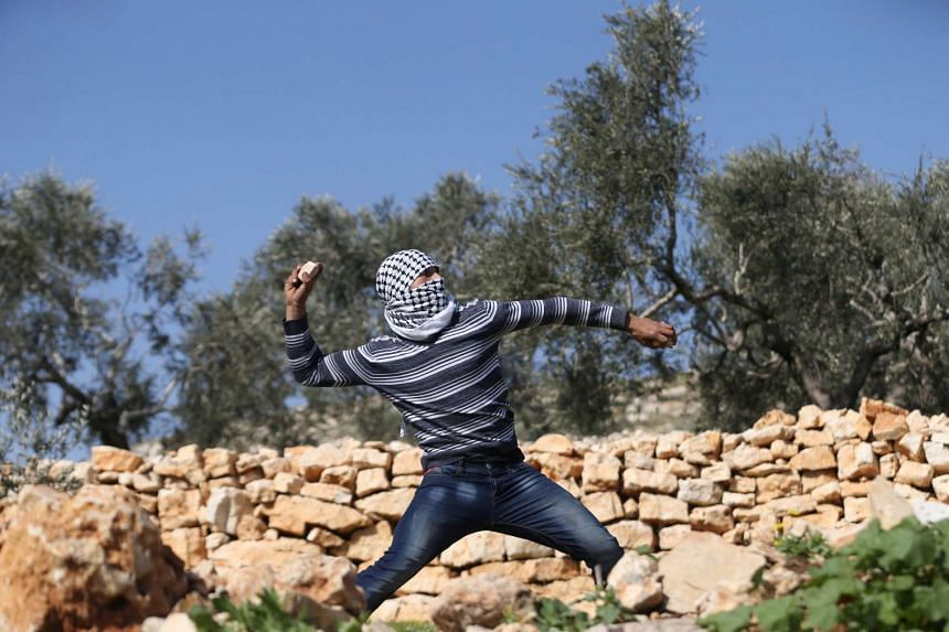 A Palestinian protester hurls stones towards Israeli troops during clashes following a protest against a Jewish settlement, Feb 10, 2017.