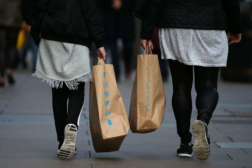 Shoppers carry their purchases in bags as they walk along a street in London, on Feb 14, 2017.