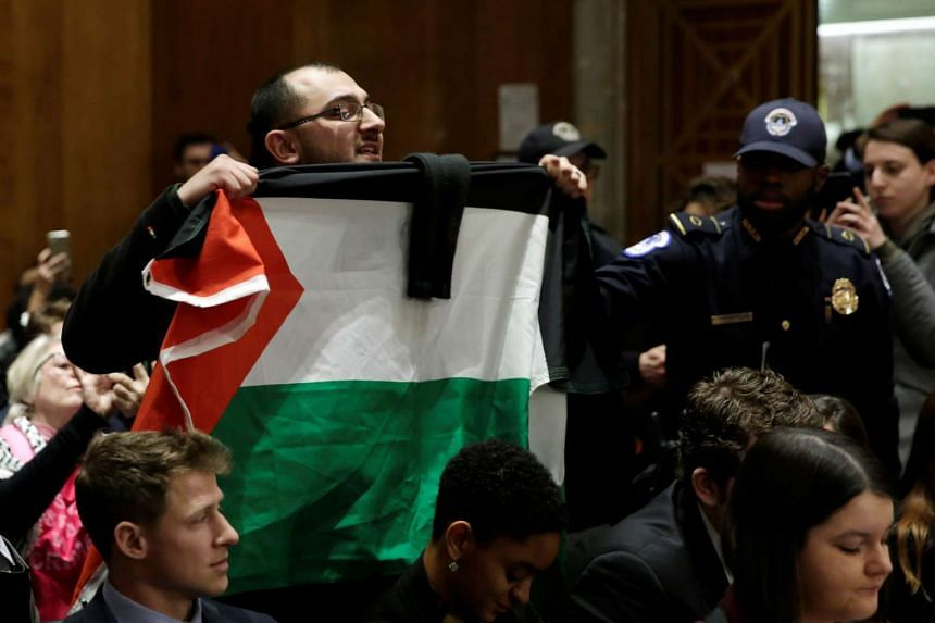 A protester holds a Palestinian flag during a Senate Foreign Relations Committee hearing on David Friedman's nomination.