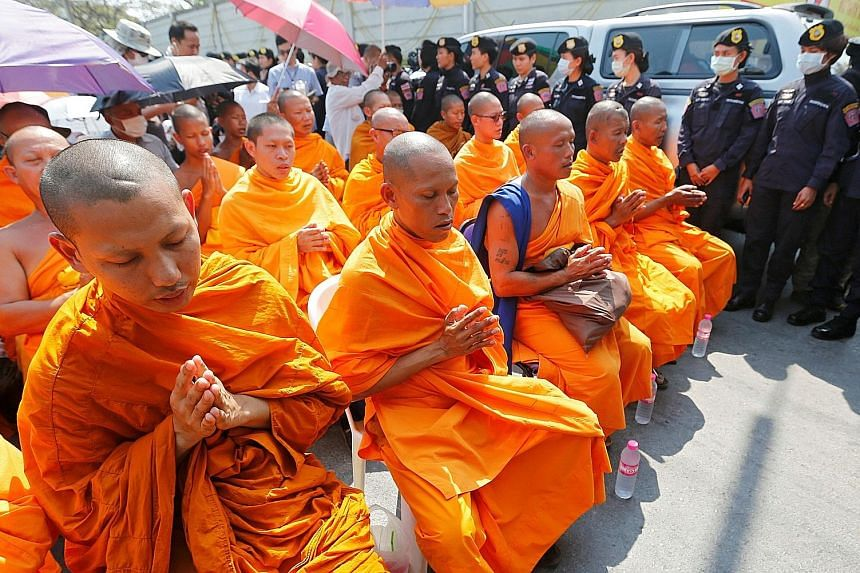 Buddhist monks chanting at Dhammakaya temple amid a massive security deployment yesterday. Prime Minister Prayut Chan-o-cha issued an order declaring the temple a controlled zone and authorised security forces to take control of any type of infrastru