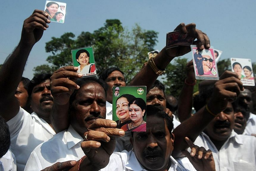 Members of AIADMK holding up portraits of Sasikala and former Tamil Nadu chief minister Jayalalithaa as they celebrated yesterday in front of the governor's residence after AIADMK legislator Edappadi K. Palaniswami was sworn in as chief minister. Mr