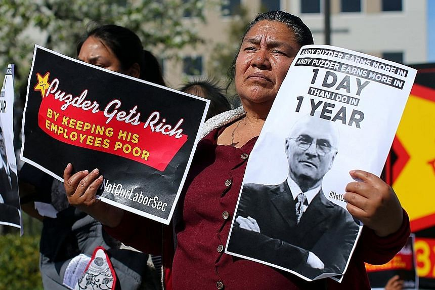 Fast-food workers in Anaheim, California, at an anti-Puzder protest on Monday. Mr Puzder's business record and character have come under attack from various groups.