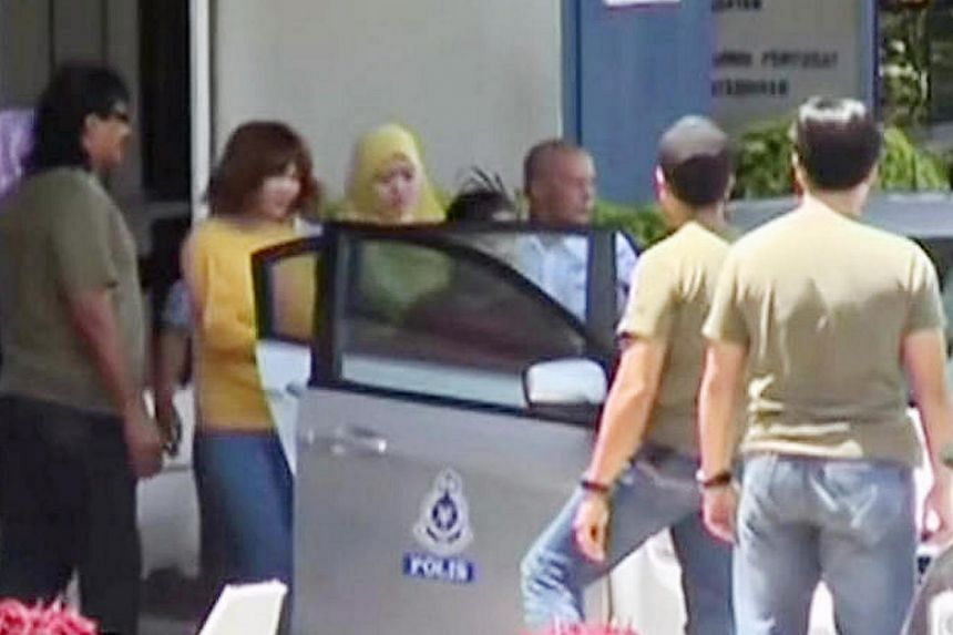 Siti Aishah (in yellow top) being escorted into a police car after another woman Doan Thi Huong was arrested a day earlier.