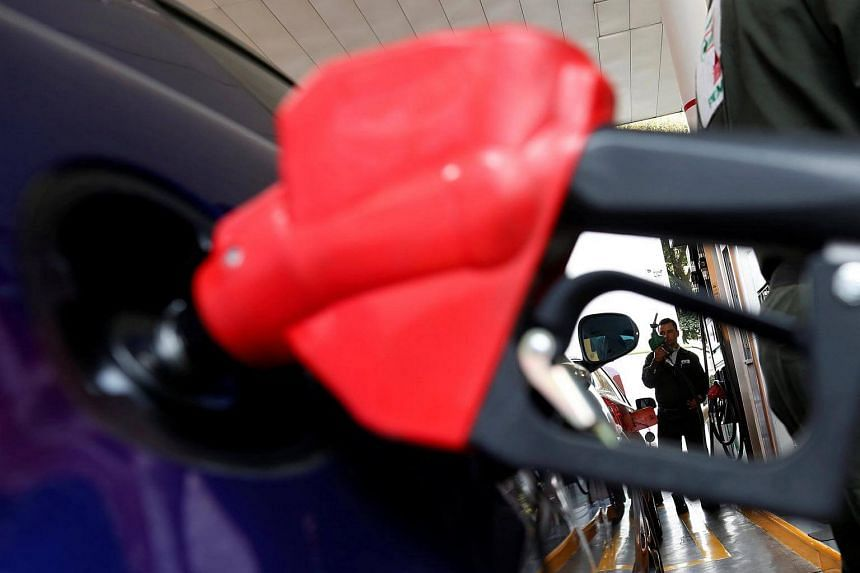 A car is being filled with fuel as a man holds a nozzle at a Pemex petrol station in Mexico City, Mexico, on Feb 3, 2017.