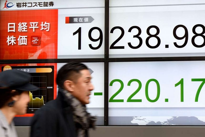 People walking past an electric quotation board flashing the Nikkei key index of the Tokyo Stock Exchange (TSE) in front of a securities company in Tokyo.