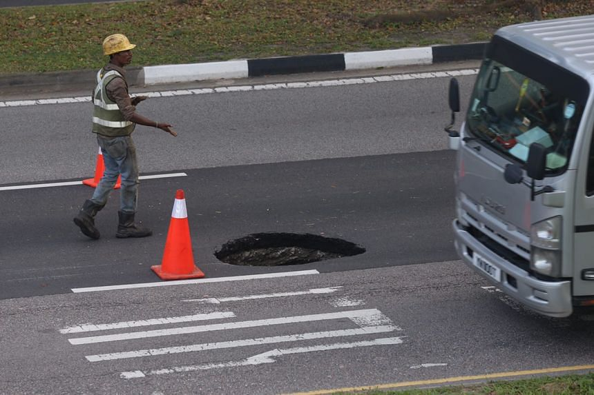 Contractors cordoned off a 1m-wide sinkhole along Ang Mo Kio Ave 5, near AMK Techplace 1, at around 6pm on Friday, Feb 17, 2017.