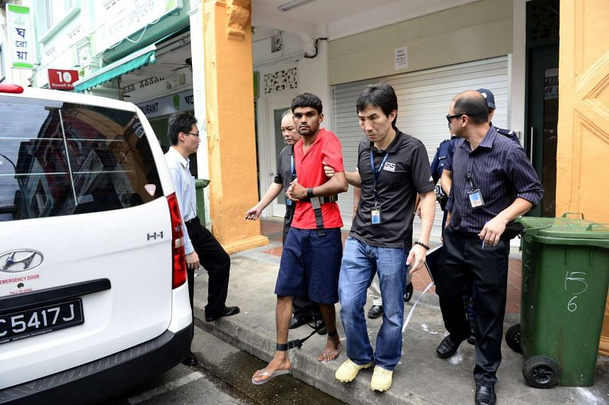 Murder suspect Ramzan Rizwan (in red) being escorted by investigators outside the lodging house at 6 Rowell Road on June 19, 2014.