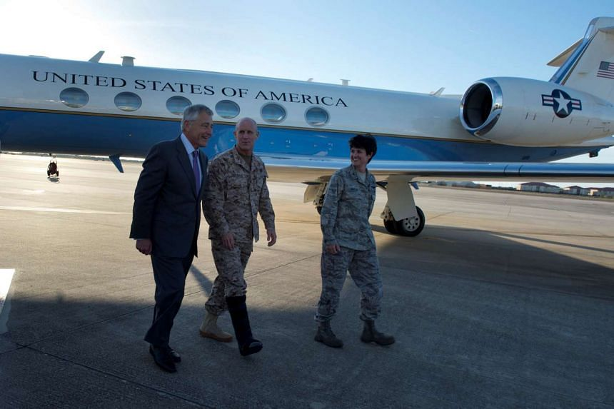Then US Secretary of Defense Chuck Hagel (left), walking with Vice Admiral Robert Harward (centre) and Colonel Kelly Martin, vice commander of 6th Air Mobility Wing, after landing at MacDill Air Force Base, Tampa, Florida, on March 21, 2013.