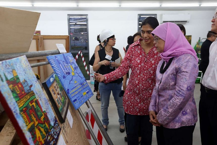 Madam Halimah Yacob looks at the artwork by Nuzhat Kazi, 47, titled A Small Serving Of Singapore.