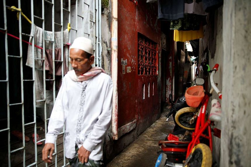 A man walks past a house (red colour) where Siti Aisyah used to live in the Tambora district of Jakarta, Feb 17, 2017.