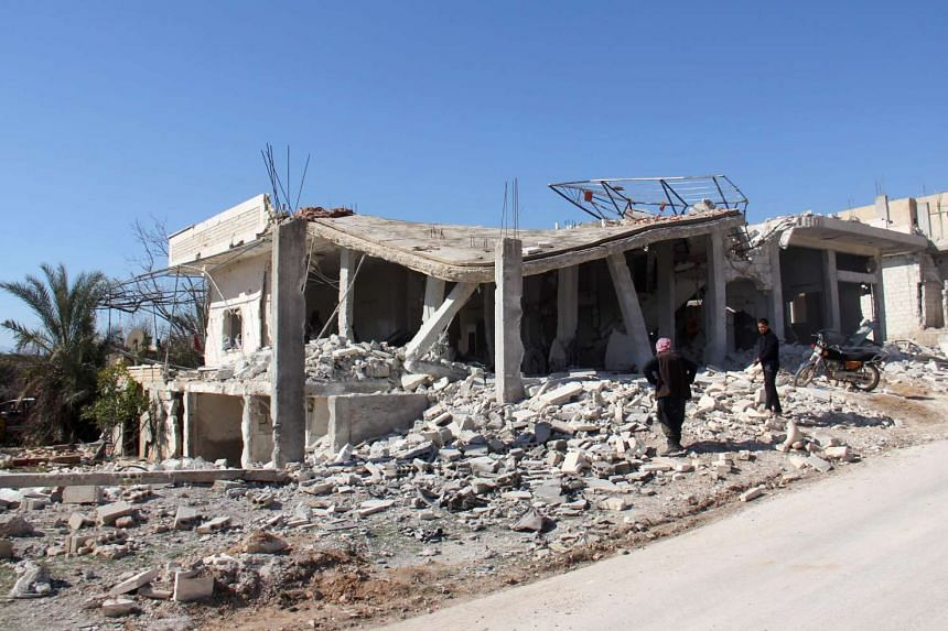 Syrian men inspecting Abdel Basset Al-Satuf's house after a barrel bomb attack in Syria's Idlib province.
