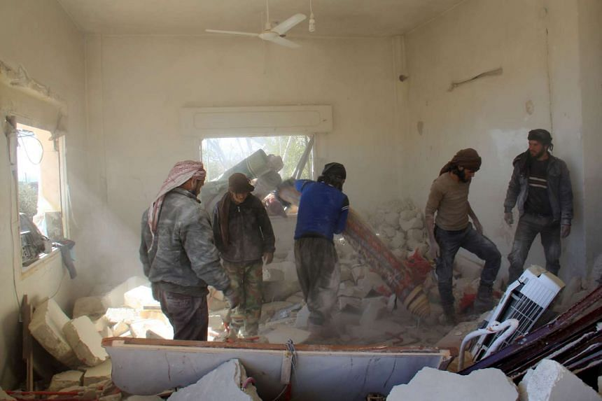 Syrian civil defence members and civilians inspecting the boy's house in the town of Al-Hbeit, in northwest Idlib province, on Feb 17, 2017, after heavy air strikes the previous day.