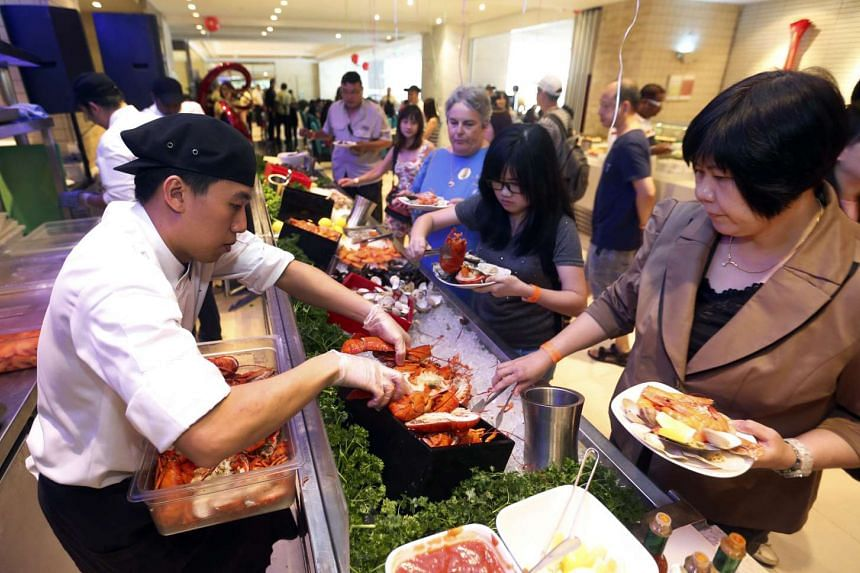 Customers picking their food at Royal Plaza on Scotts' buffet restaurant Carousel during the pay-as-you-wish buffet lunch on Feb 18, 2017.
